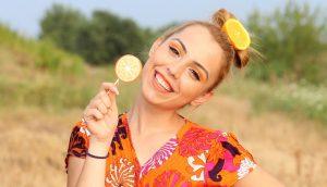 Rubia comiendo barra de caramelo de naranja
